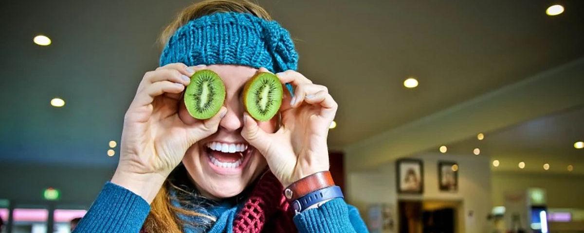 Новозеландка держит киви фрукт