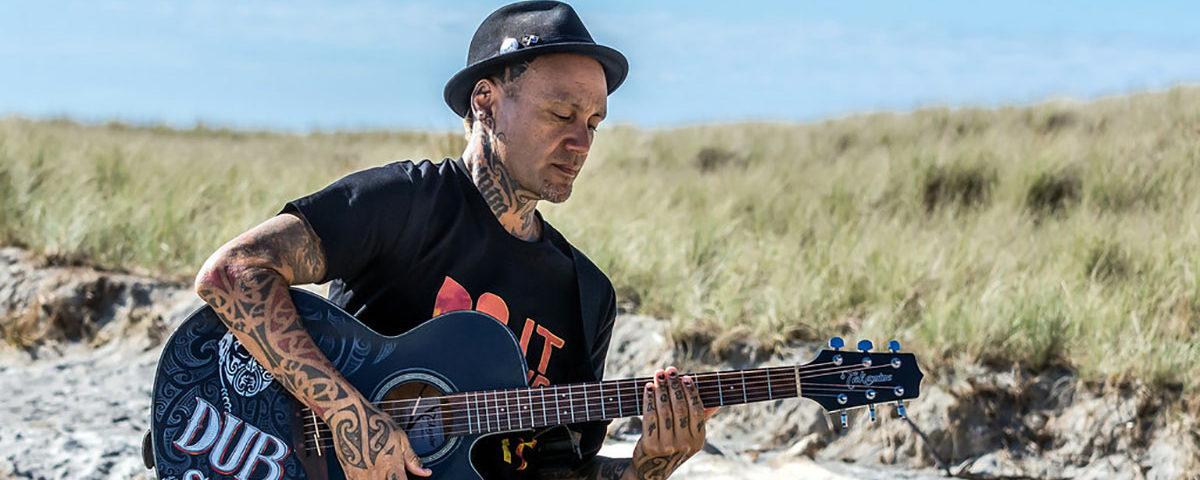 Музыкант с гитарой на пляже