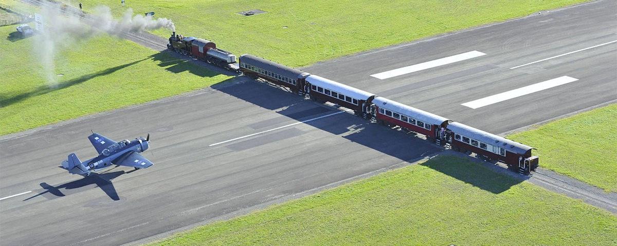 Самолет взлетает над поездом